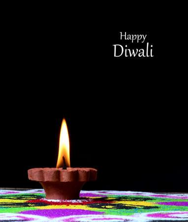 Clay diya lamps lit during diwali celebration, Rangoli in background