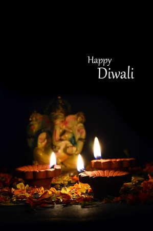 Clay diya lamps lit with Lord Ganesha during Diwali Celebration. Greetings Card Design Indian Hindu Light Festival called Diwali Stock Photo