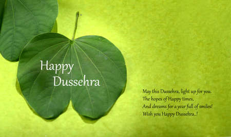 Indian Festival Dussehra, showing golden leaf and flowers on green background. Greeting card. Stock Photo