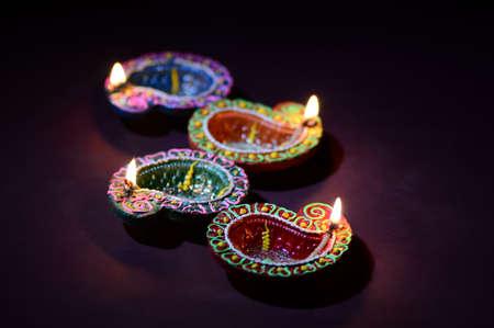 Colorful clay Diya (Lantern) lamps lit during Diwali celebration. Greetings Card Design Indian Hindu Light Festival called Diwali. Banco de Imagens