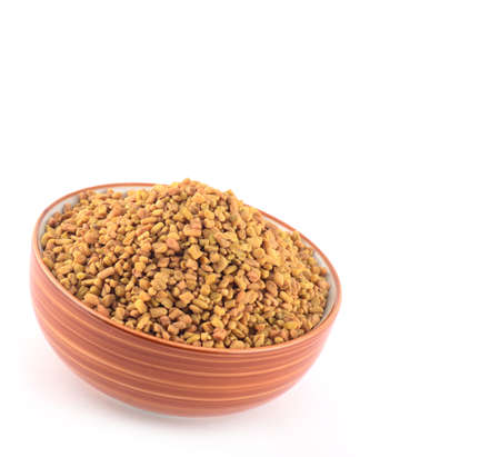 Fenugreek seeds in bowl isolated on white background