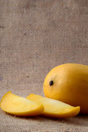 Mango fruit with slice on sack cloth background