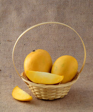 Mango fruit in basket on sack cloth background