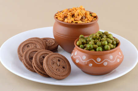 Bocadillo indio: Mezcla, galleta de crema y guisantes verdes fritos condimentados {chatpata matar} en un plato.