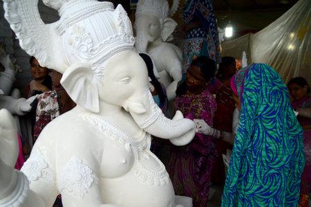 MUMBAI, MAHARASHTRA - 24 AUGUST 2014 : Artist gives finishing touches on an idol of the Hindu god Lord Ganesha at an artists workshop for Ganesha-festival, 24 August 2014, Maharashtra, India. Editorial