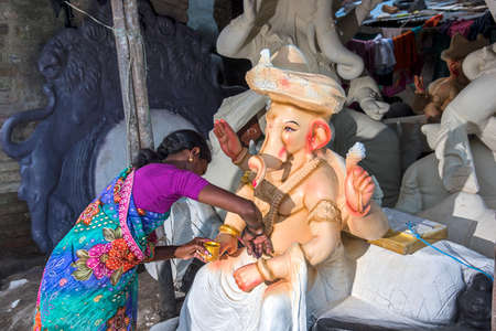 AMRAVATI, MAHARASHTRA - SEPTEMBER 4, 2016: Artist making a statue and gives finishing touches on an idol of the Hindu god Lord Ganesha at an artists workshop for Ganesha festival.