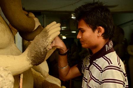 NAGPUR, MAHARASHTRA - 3 AUGUST 2014 : Artist gives finishing touches on an idol of the Hindu god Lord Ganesha at an artists workshop for Ganesha-festival, 3 August 2014, Maharashtra, India. Editorial