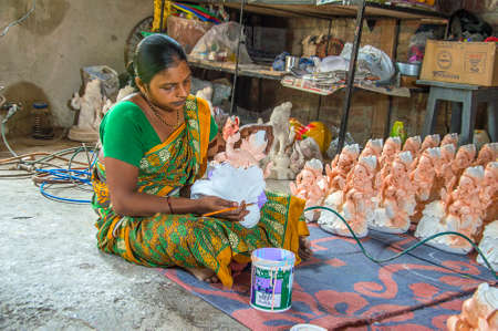 AMRAVATI, MAHARASHTRA - 26 AUGUST 2016 : Artist gives finishing touches on an idol of the Hindu god Lord Ganesha at an artists workshop for Ganesha-festival, 26 August 2016, Maharashtra, India. Editorial