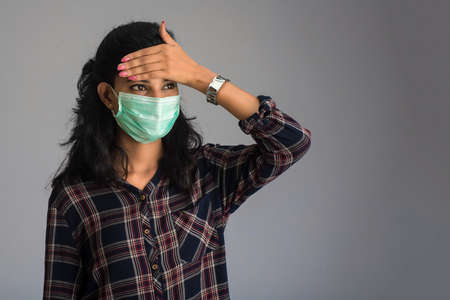 Beautiful woman having a fever wearing a medical mask feeling sick and ill.