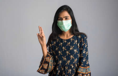 Young woman wearing medical face mask Showing sign. Woman wearing surgical mask for corona virus.