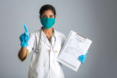 Coronavirus concept for a blood test. A young woman doctor reading or filling a medical test form for coronavirus testing.