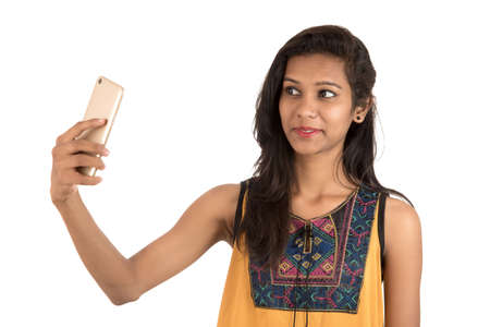 Portrait of a happy young girl using mobile phone isolated over white background