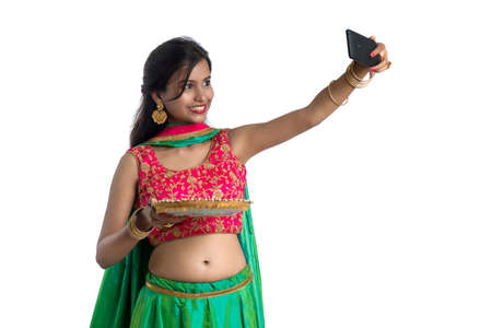 Beautiful young happy girl taking a selfie with clay lamp or diya during the festival of light Diwali using a smartphone on a white background