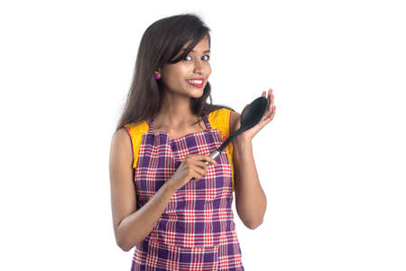 Young Indian woman holding kitchen utensil (spoon, stapula, ladle, and pan, etc.) on a white background