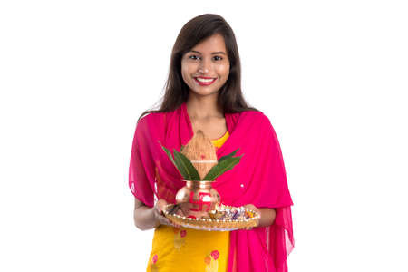 Indian girl holding a traditional copper Kalash with Pooja Thali, Indian Festival, copper Kalash with coconut and mango leaf with floral decoration, essential in Hindu Pooja.