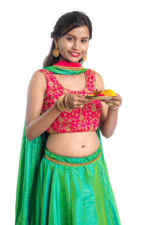 Beautiful Indian young girl holding pooja thali or performing worship on a white background Stock Photo