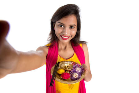 Beautiful young happy girl taking selfie with pooja thali using a mobile phone or smartphone on a white background Stock Photo