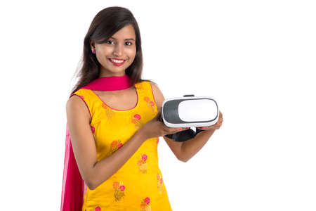 Indian traditional young girl holding and showing VR device, vr box, goggles, 3D Virtual Reality Glasses headset, Girl with Modern imaging Future technology on white background.