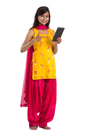 Young Indian girl using a mobile phone or smartphone isolated on a white background