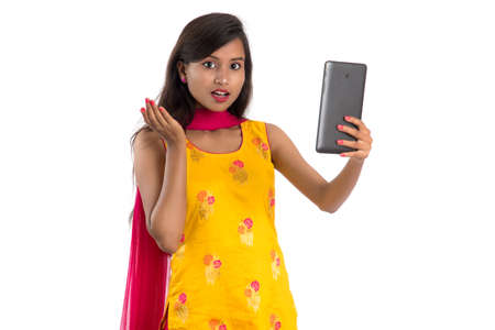 Young Indian girl using a Tablet, mobile phone or smartphone isolated on a white background Stok Fotoğraf