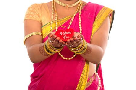 Traditional Beautiful Indian young girl in saree posing with Heart on white background