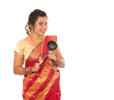 Young Traditional Indian Girl holding kitchen utensil on white background
