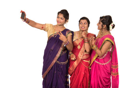 Indian traditional girls taking selfie with smartphone on white background