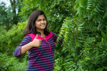Jeune fille examiner ou observer le Neem (Azadirachta indica) Feuille d'arbre au champ