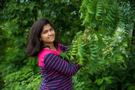 Jeune fille examiner ou observer le Neem (Azadirachta indica) Feuille d'arbre au champ Banque d'images