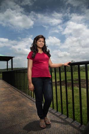 Portrait of beautiful young girl on the bridge near lake. 写真素材
