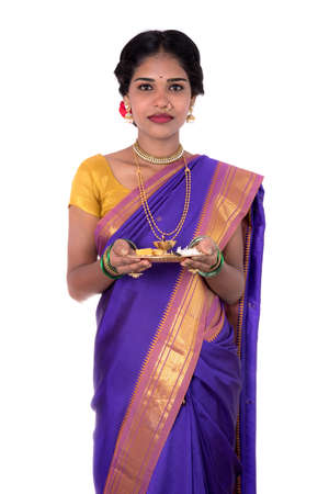 Indian woman performing worship, portrait of a beautiful young lady with pooja thali isolated on white background Stock Photo