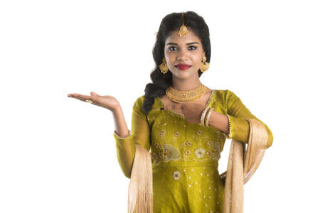 Portrait of cheerful Indian traditional young woman presenting something, showing copy space on her palm on a white background