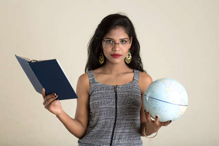 Young girl student holding book with globe on white background. Education in high school university college concept