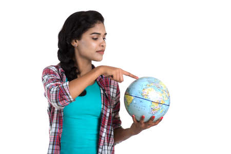 young woman holding the world globe and posing on a white background.