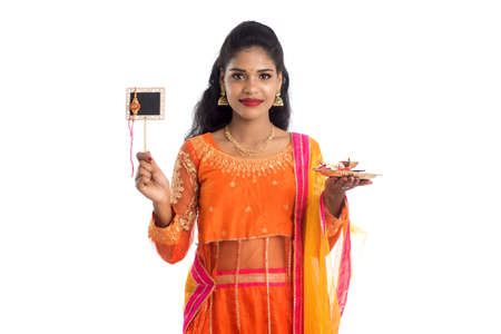 Beautiful Indian girl showing Rakhi on occasion of Raksha Bandhan with pooja thali and black board. Sister tie Rakhi as a symbol of intense love for her brother.