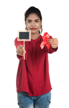 Young woman showing red ribbon HIV, AIDS awareness ribbon, healthcare and medicine concept