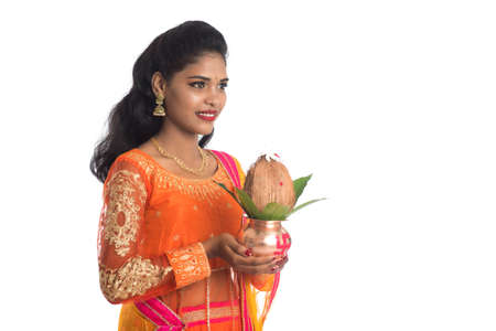 Indian Woman holding a traditional copper kalash, Indian Festival, copper kalash with coconut and mango leaf with floral decoration, essential in hindu puja.