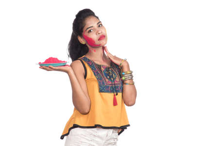 Beautiful young girl holding powdered color on a plate and enjoying colors on the occasion of the Holi festival. Stock fotó
