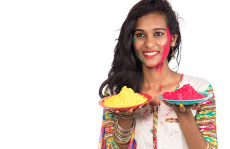 Beautiful young girl holding powdered color in plate on the occasion of Holi festival.