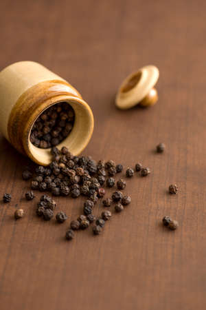 Close up of black pepper or peppercorns with clay pot on a wooden background. Zdjęcie Seryjne
