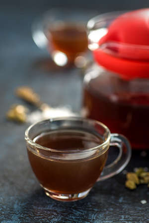 A cup of tea and cardamom with sugar in a spoon on a textured background. Фото со стока
