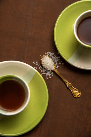 Cups of tea with sugar in a spoon on a wooden background.
