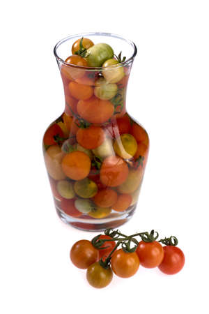 Fresh cherry tomato in glass jar with tomatoes on branch isolated on white background. Stock fotó