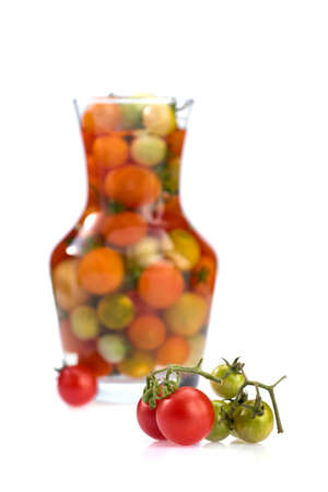 Fresh cherry tomato in glass jar with tomatoes on branch isolated on white background. 版權商用圖片