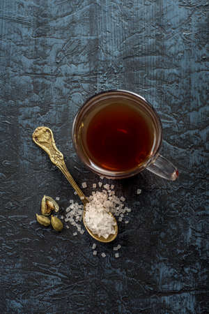 A cup of tea and cardamom with sugar in a spoon on a textured background. Stock fotó