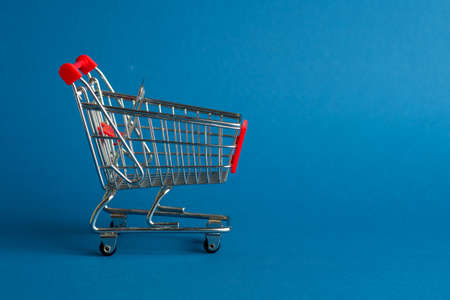 The empty cart or shopping cart for purchases on blue background.