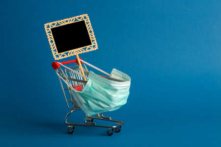 Supermarket cart for shopping. The trolley is wearing a medical mask. virus control concept. Creative idea for an online pharmacy, online drug sale.