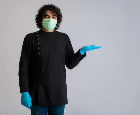Young man wearing a medical face mask Showing something on hand. a man wearing a surgical mask for protection from virus.