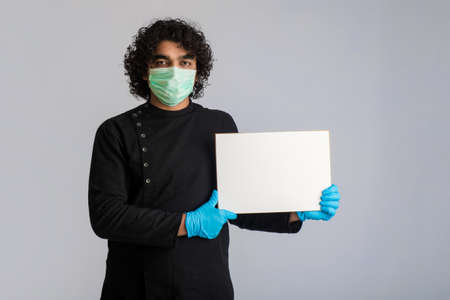 A young man in a medical mask holding and showing a blank board
