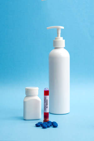 Bottle of pills with tablets with sanitizer bottle and test tube filled with a blood sample for testing . Coronavirus pandemic epidemic concept. 版權商用圖片